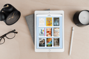 E-book app on an iPad, sitting on a desktop with an Apple pencil, glasses, candle, clock, and glasses